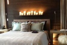 11 a wood clad black headboard wall is highlighted with a row of candles on a ledge