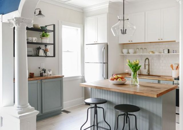 lower dove grey cabinets and white uppers with natural wood countertops for a cozy natural feel