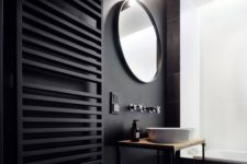 12 a black wall with a black radiator and black tiles on another wall, mosaic geometric tiles on the floor