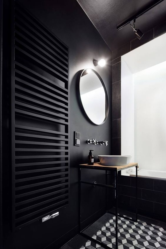 a black wall with a black radiator and black tiles on another wall, mosaic geometric tiles on the floor