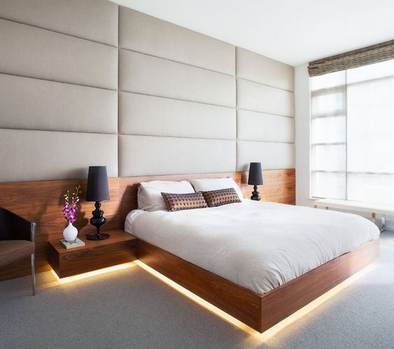 a creamy upholstered wall, a floating wooden bed with nightstands with lights coming from below
