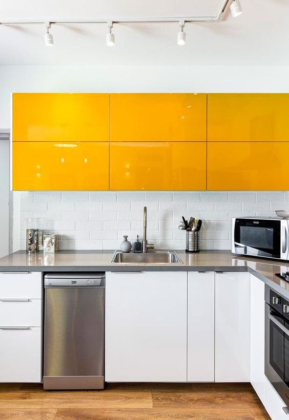 a minimalist yellow and white kitchen with stainless steel appliances and countertops and a subway tile backsplash
