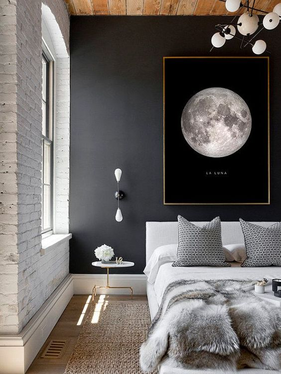 a modern space with an industrial feel is made more interesting with a black wall with an artwork and a white brick wall