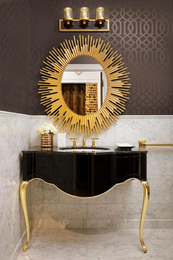a refined black and gold bathroom vanity and a sunburst mirror is a great idea for a refined art deco space