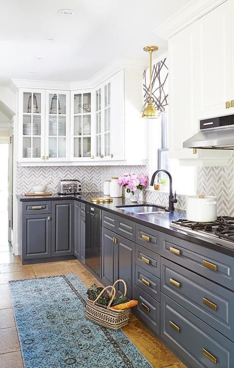 a vintage-styled kitchen with white and grey cabinets, brass touches and a black countertop