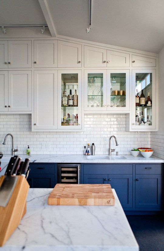 a chic kitchen with white uppers and electric blue lower cabinets plus a subway tile backsplash in white