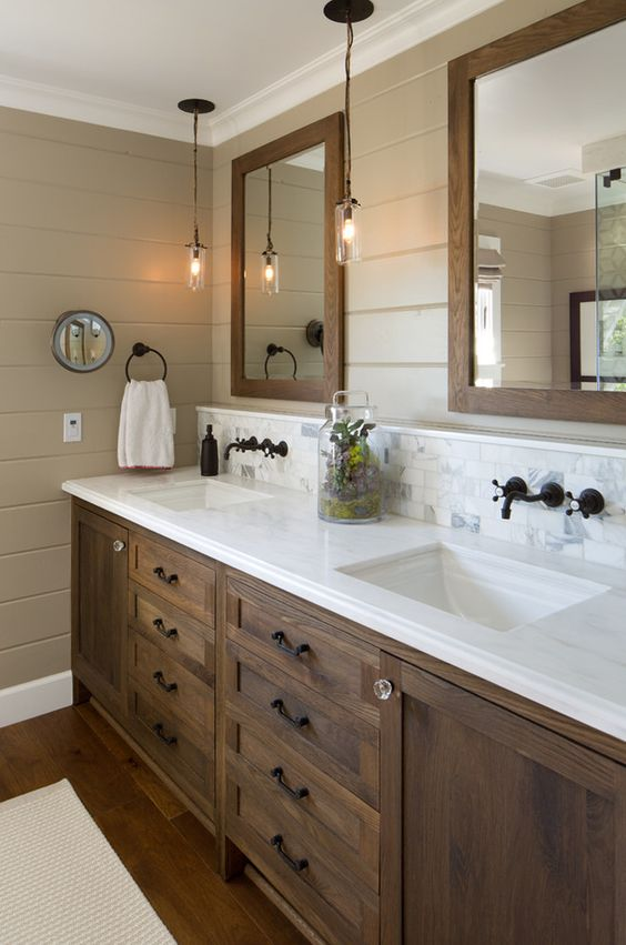 a double stained wooden vanity with a white marble countertop and matching mirror frame