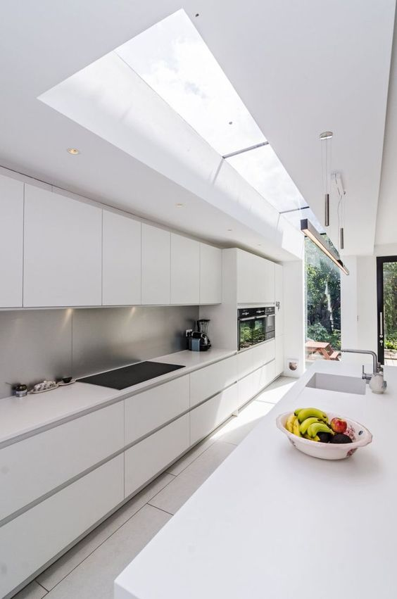 a long narrow minimalist white kitchen with a metal backsplash and skylights to bring much light in