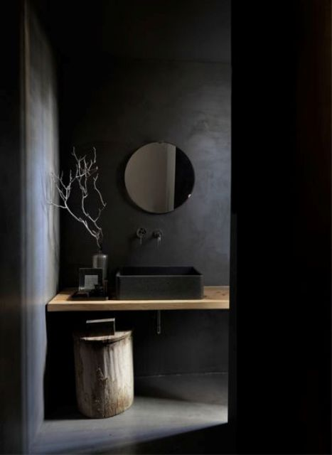 a moody bathroom with black walls and floor, a black sink and a wooden shelf-style vanity
