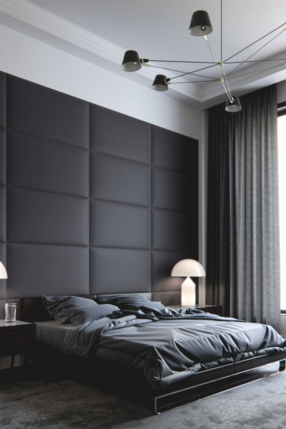 a moody space with a black upholstered wall, a dark bed and dark linens, curtains and a rug that match