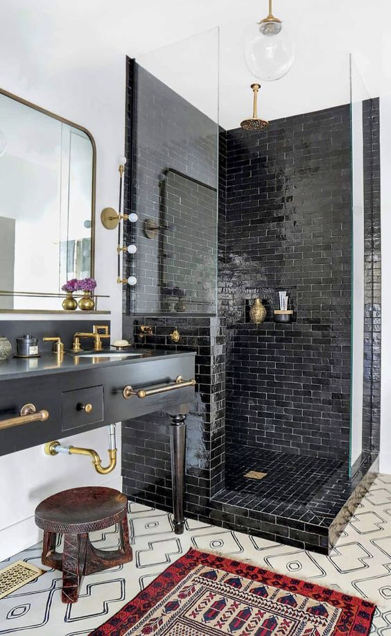 a vintage-inspired matte black vanity with brass fixtures with vintage legs and other brass touches to tying the parts