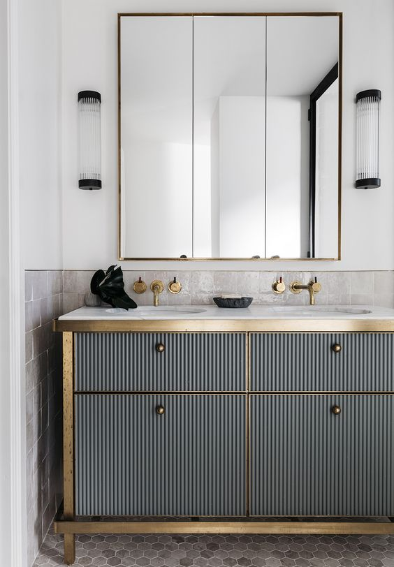 a corrugated metal vanity with brass touches looks very bold and interesting, art deco though modern
