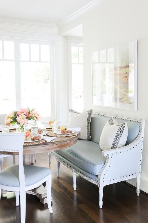 a cut pale blue bench and chairs for a coastal dining space with a rustic wooden table