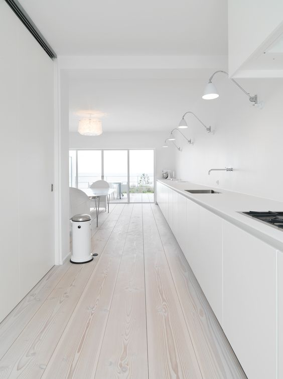 a large long minimalist white kitchen with only floor cabinets and whitewashed floors