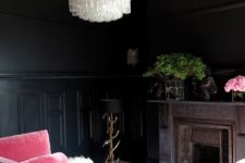 a luxurious moody living room with black walls, a crystal chandeliers, a pink sofa and a vintage fireplace