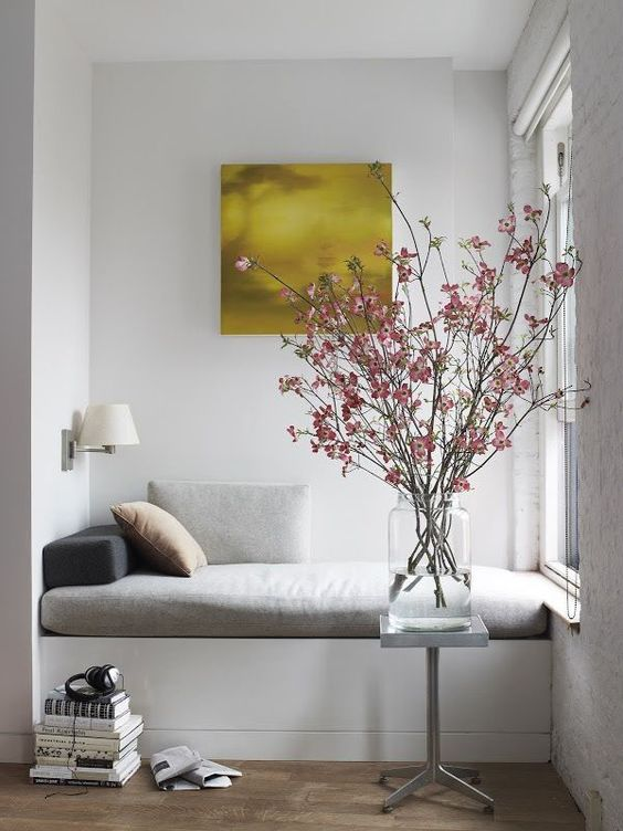 a small nook by the window is taken by a daybed with pillows and upholstery, great for reading and having a nap