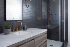 14 black long tiles with black grout for cladding walls, geometric black and white tiles on the floor for a bold modern look