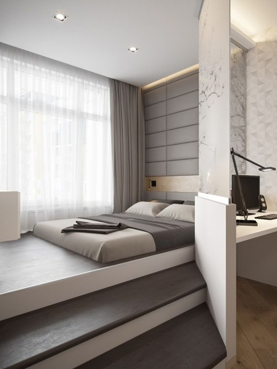 a grey upholstered wall, matching linens and a glass partition that separates the sleeping space form the working one