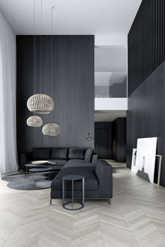a minimalist space with black wooden walls and furniture, cool pendant lamps highlight the double height ceiling