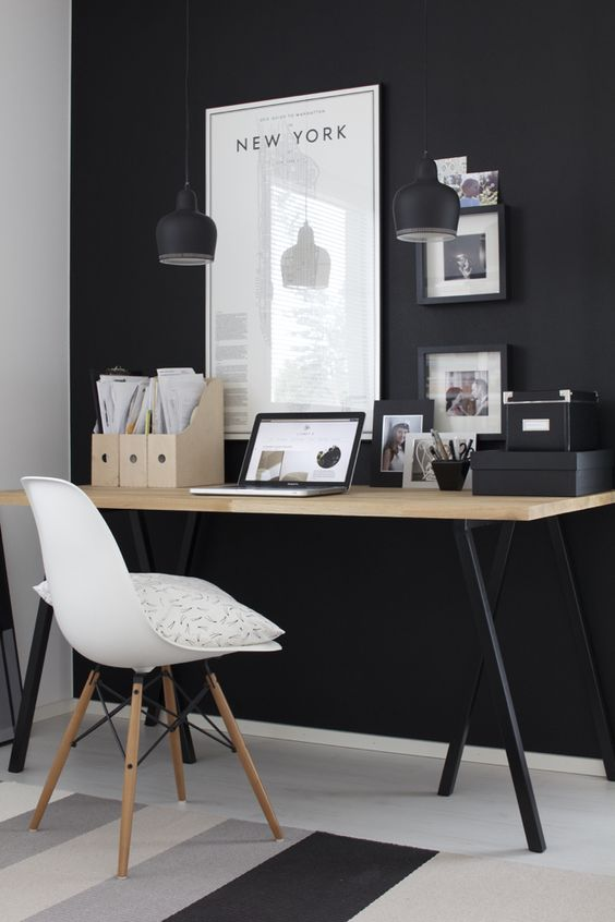 a modern Scandi space with a black wall, artworks and a wooden desk with black legs
