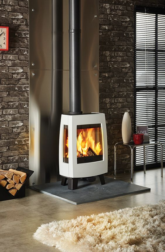 a modern industrial interior is made cozier and more chic with a gorgeous free standing stove with a chic design