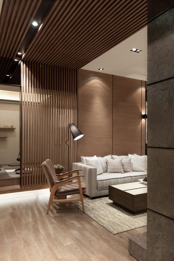 a modern living room with a wooden wall, the part of which is of planks that create a space divider