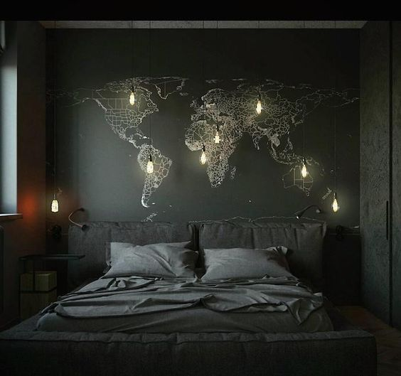 a moody space with a black wall and a world map on it, a black upholstered bed and some hanging bulbs
