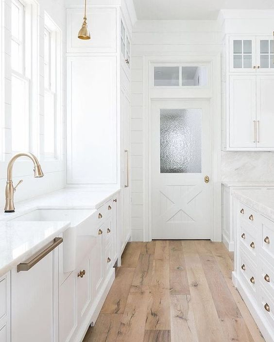 a vintage white kitchen with brass handles and wooden floors that make it cozier