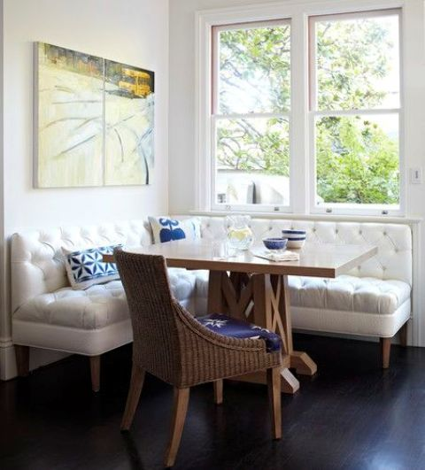 a white diamond upholstery corner bench contrasts a wicker chair and a wooden table