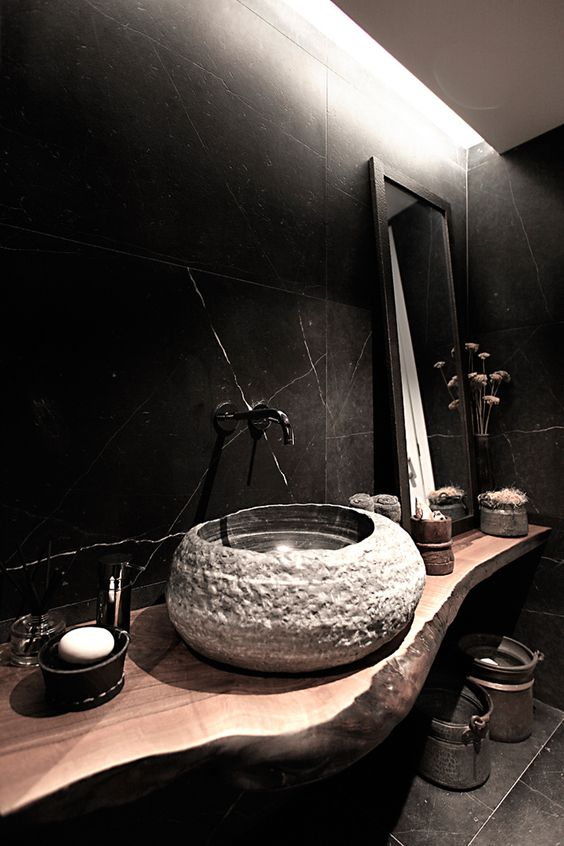 black marble tiles cladding the walls of the bathroom give it a moody feel