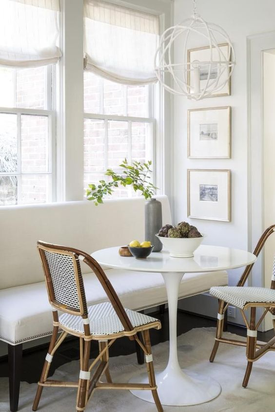 a classic white bench and wicker chairs that make up a cool and cozy breakfast nook