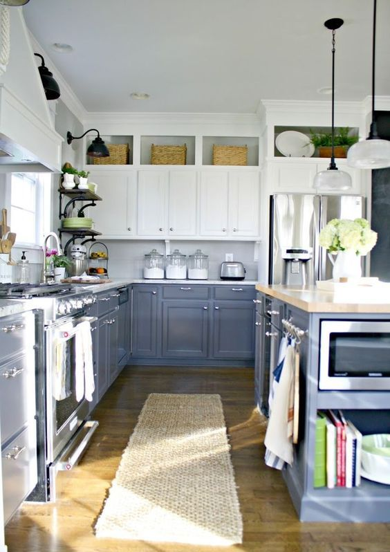 a framhouse styled kitchen with grey and white cabinets, wicker touches and vintage lamps