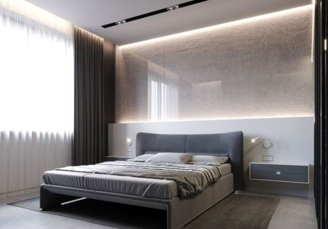 a gorgeous textural light-colored wall with additional lighting and an upholstered grey bed and floating nightstands