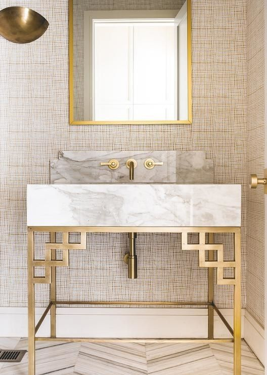 a marble and brass bathroom vanity with geometric decor and fixtures looks gorgeous