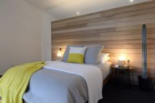 16 a modern bedroom is completed with a light-colored wooden wall and matching floor