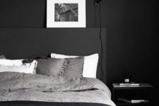 17 a Scandinavian masculine bedroom with a black wall, bed and bedding looks inviting and relaxing