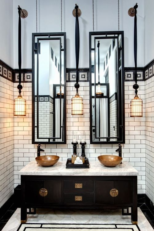 a black double vanity with dark brass touches and a marble counter for a 1920s bathroom