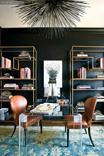a chic shared home office with a statement black wall, an acrylic desk and brass touches