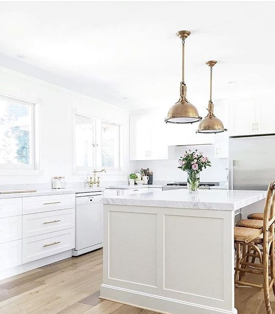 a farmhouse kitchen with brass vintage touches and marble countertops for an eye-catchy touch
