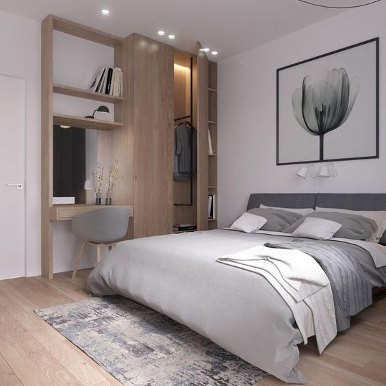 a modern bedroom in white and light grey, wooden floors and a wooden wall item with a wardrobe and desk