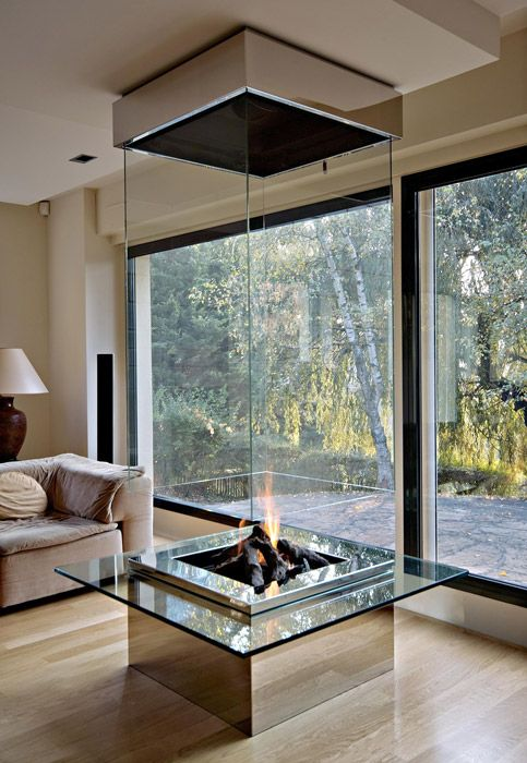 a modern fireplace with clear glass sides to be seen from every part of the house