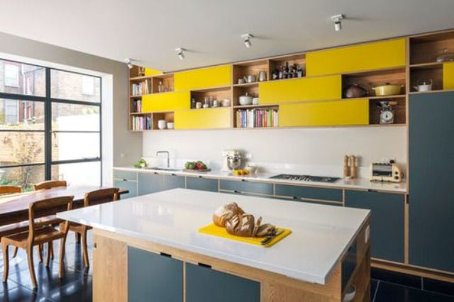 navy and yellow kitchen cabinets with a neutral backsplash and counters look contrasting and chic