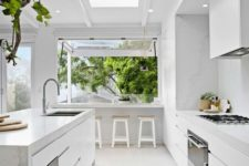 18 a light white kitchen with marble surfaces and a large window that is extended outdoors as a meal space