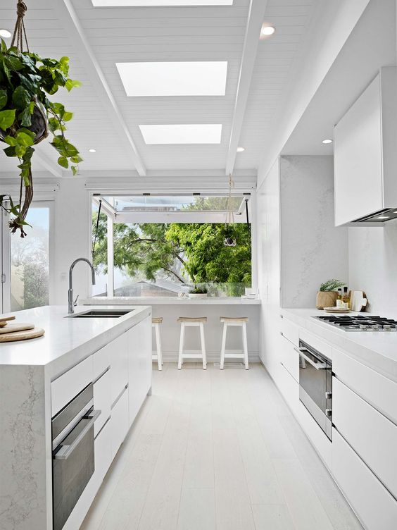 a light white kitchen with marble surfaces and a large window that is extended outdoors as a meal space