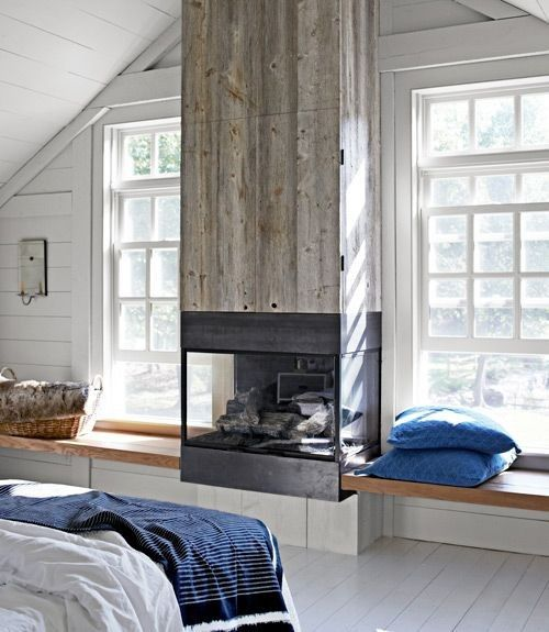 a modern cottage with a fireplace clad with reclaimed wood to add texture to the space