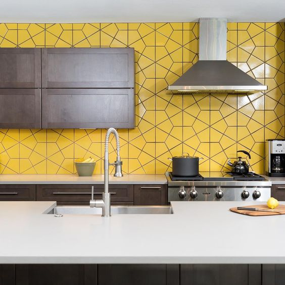 a modern dark kitchen with a whole wall taken by yellow tiles looks very bold and unusual