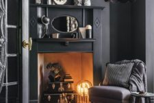 18 a modern space with a vintage feel, black walls and furniture, a faux fireplace with a unique lamp and some vintage accessories