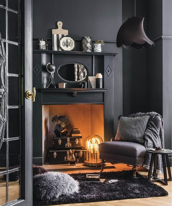 a modern space with a vintage feel, black walls and furniture, a faux fireplace with a unique lamp and some vintage accessories