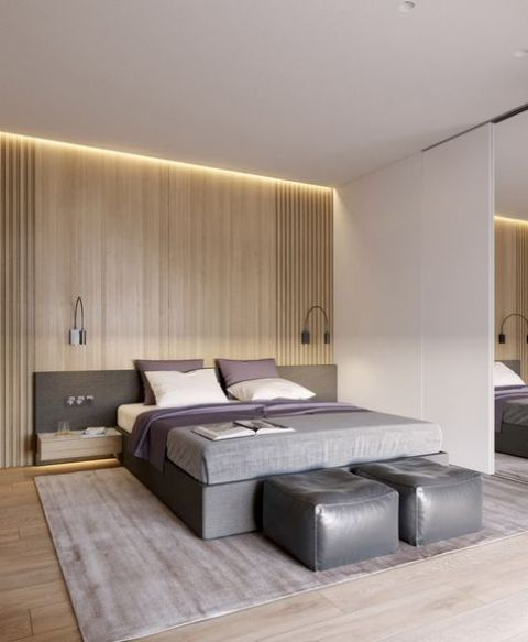 a modern space with light-colored wooden wall and floor, an upholstered grey bed with a headboard and grey leather poufs
