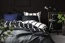 18 a vintage space with a black wall, a frame picture, some vintage items for decor and a plant to enliven the space
